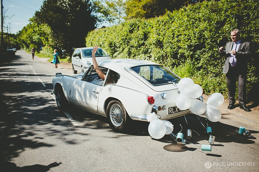 Bride and groom leave in wedding car