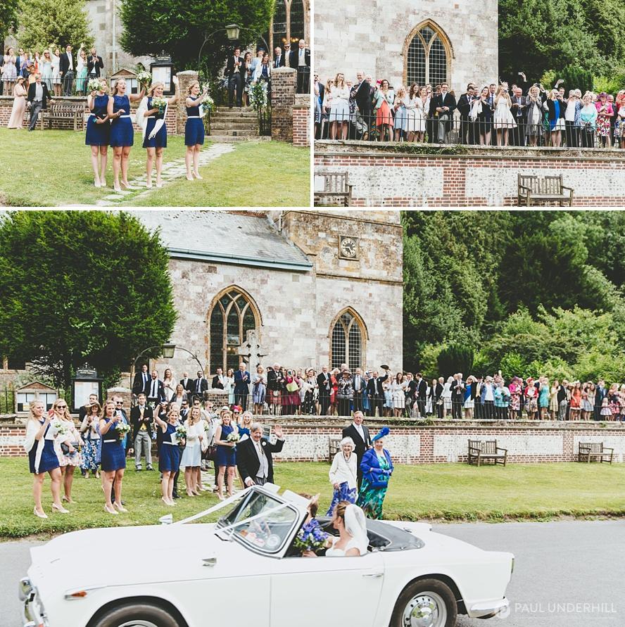 Bride and groom drive off in vintage wedding car