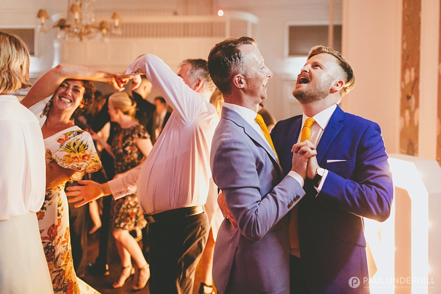 Candid photo of grooms dancing