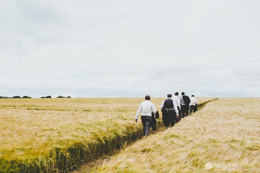 Groom walks across farm in Dorset