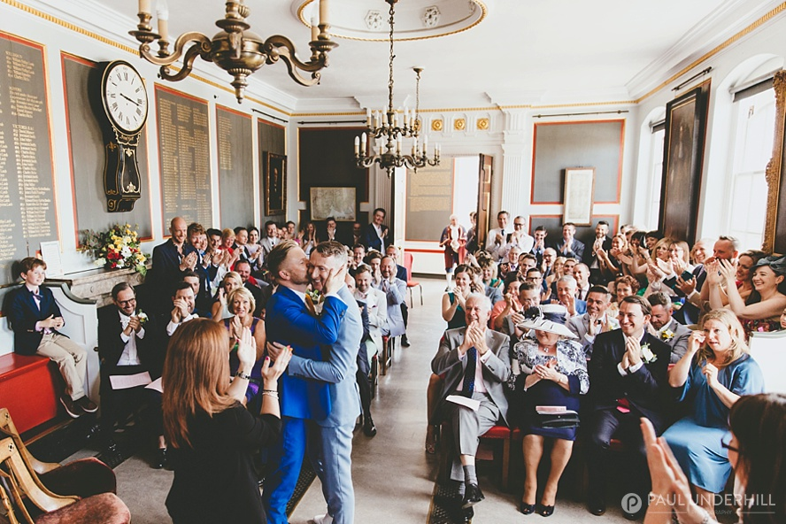 Grooms kiss same sex wedding