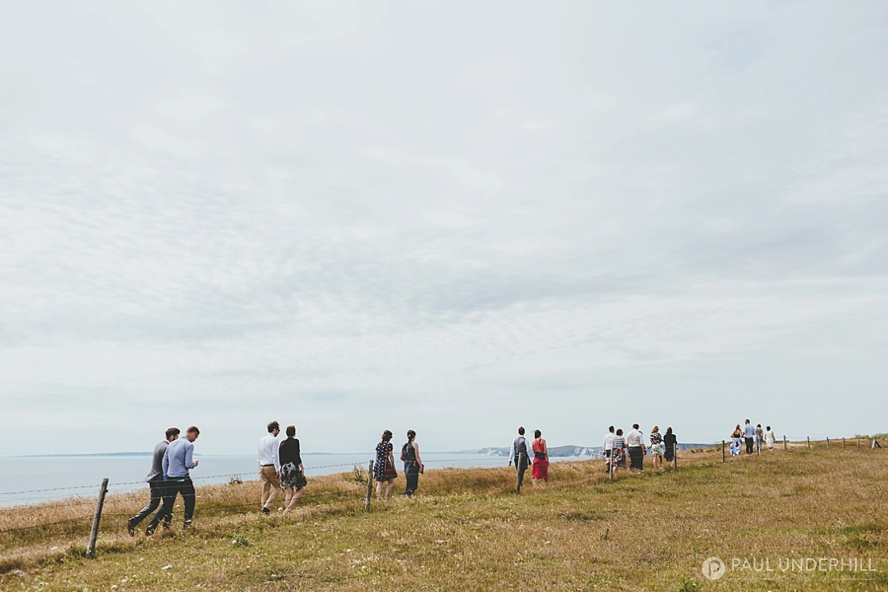 Wedding guests walk over the coast path