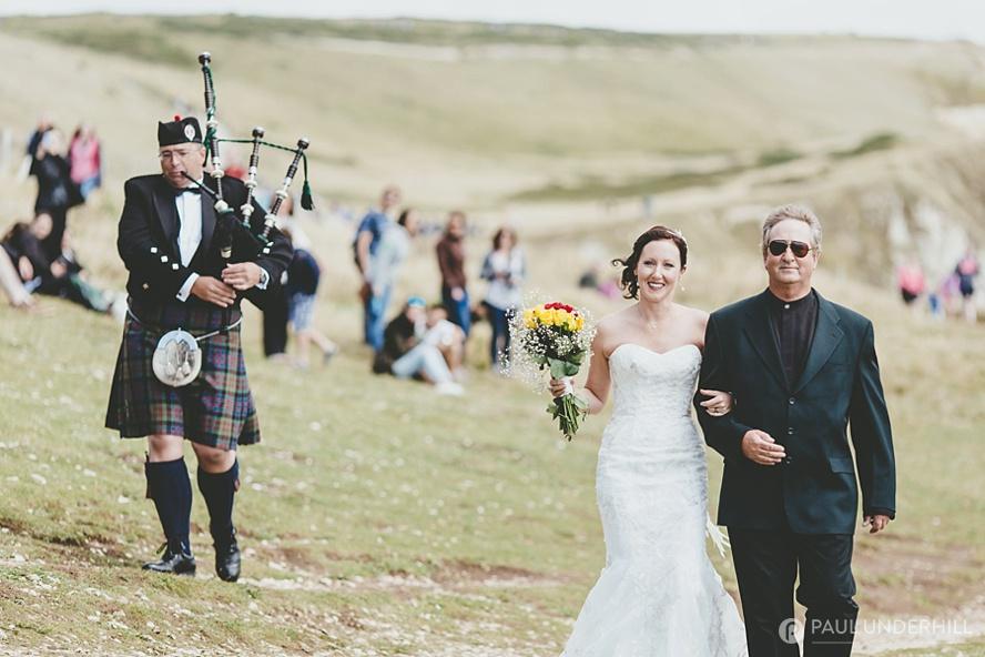 Bride arrives with bagpiper at Durdle Door wedding