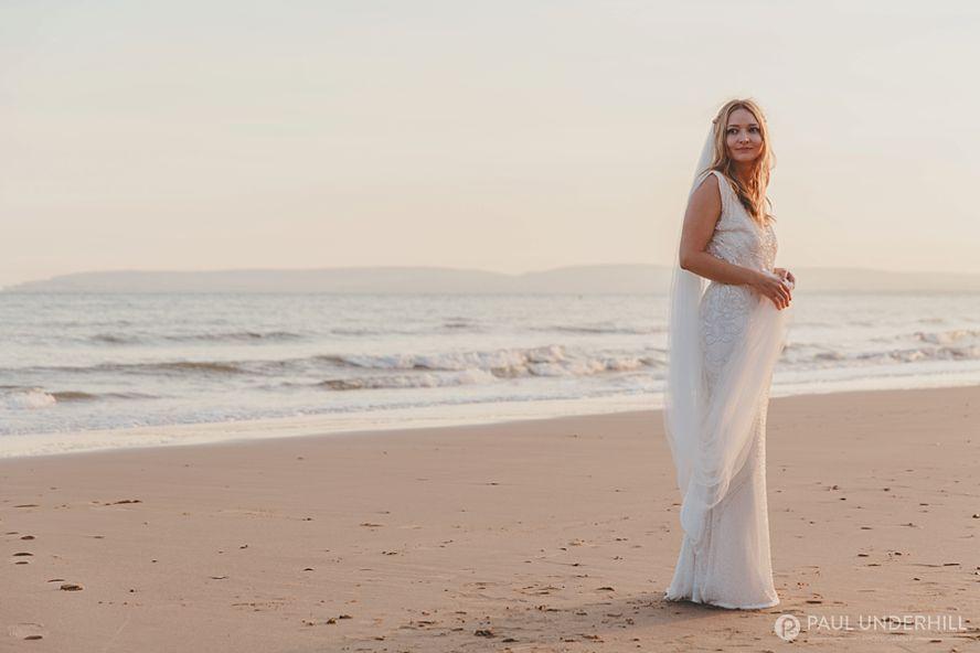 Creative wedding portrait of bride on the beach