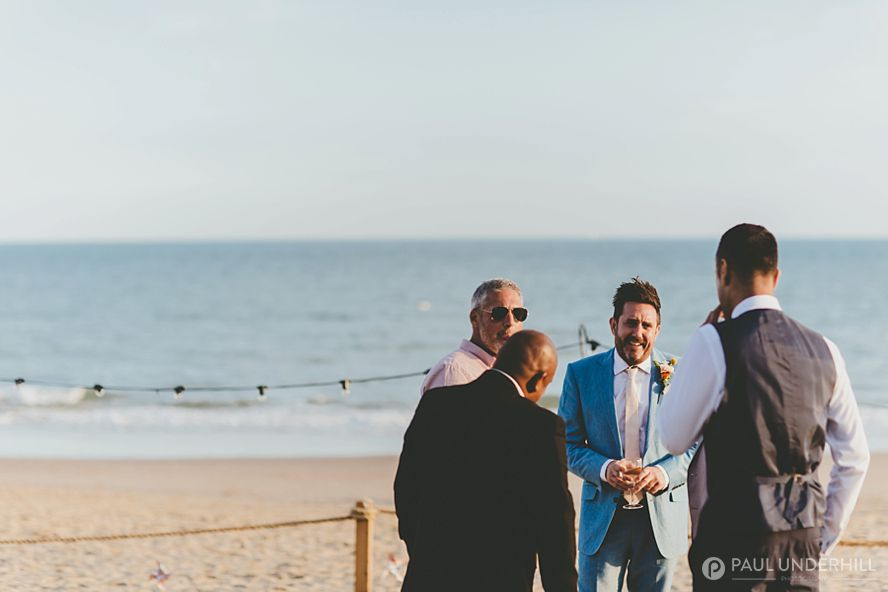 Groom and friends relaxing at beach wedding