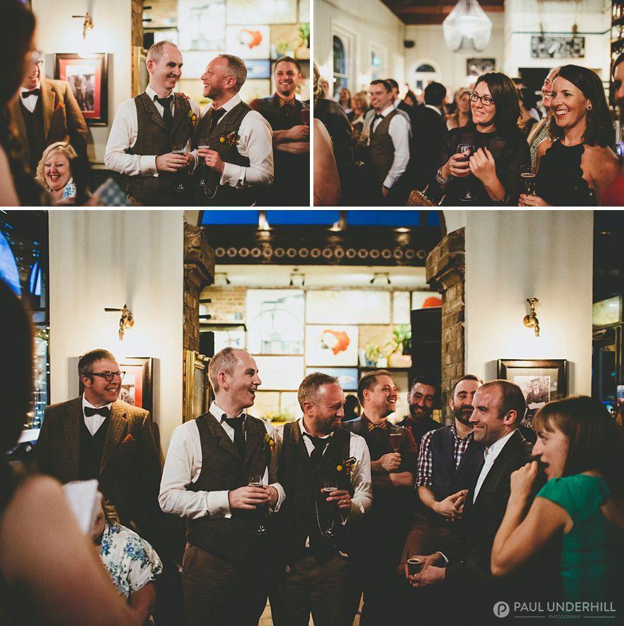 Grooms laugh during wedding speech